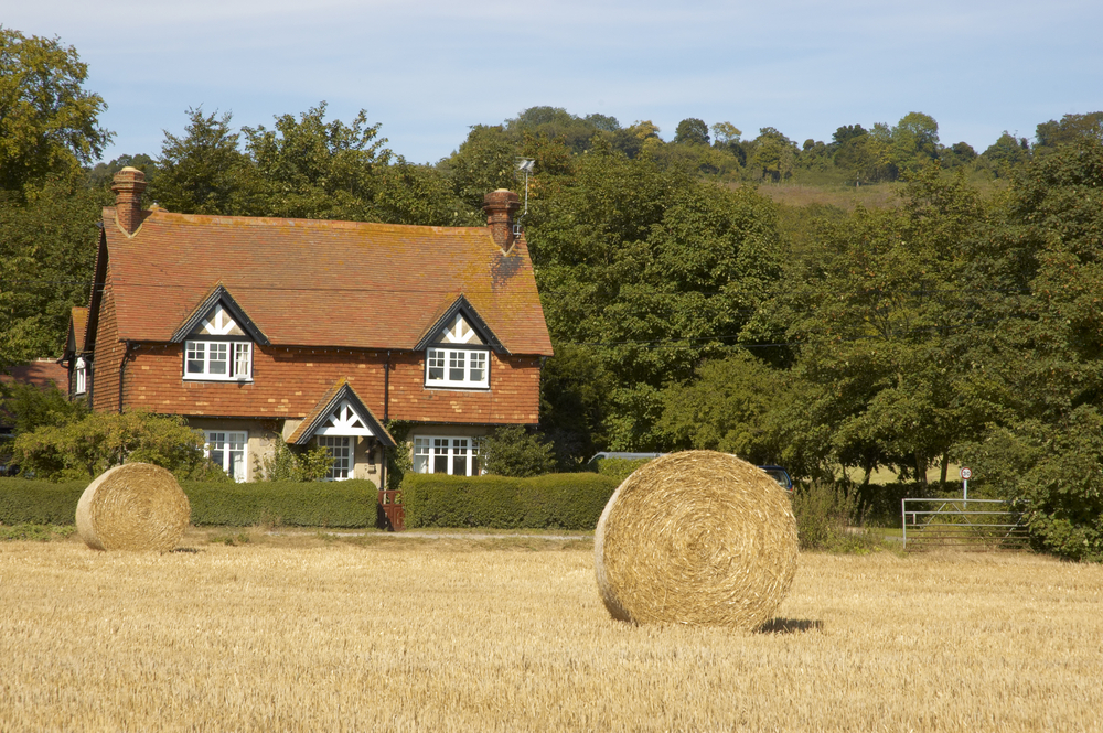 country house with hay bails in front of it