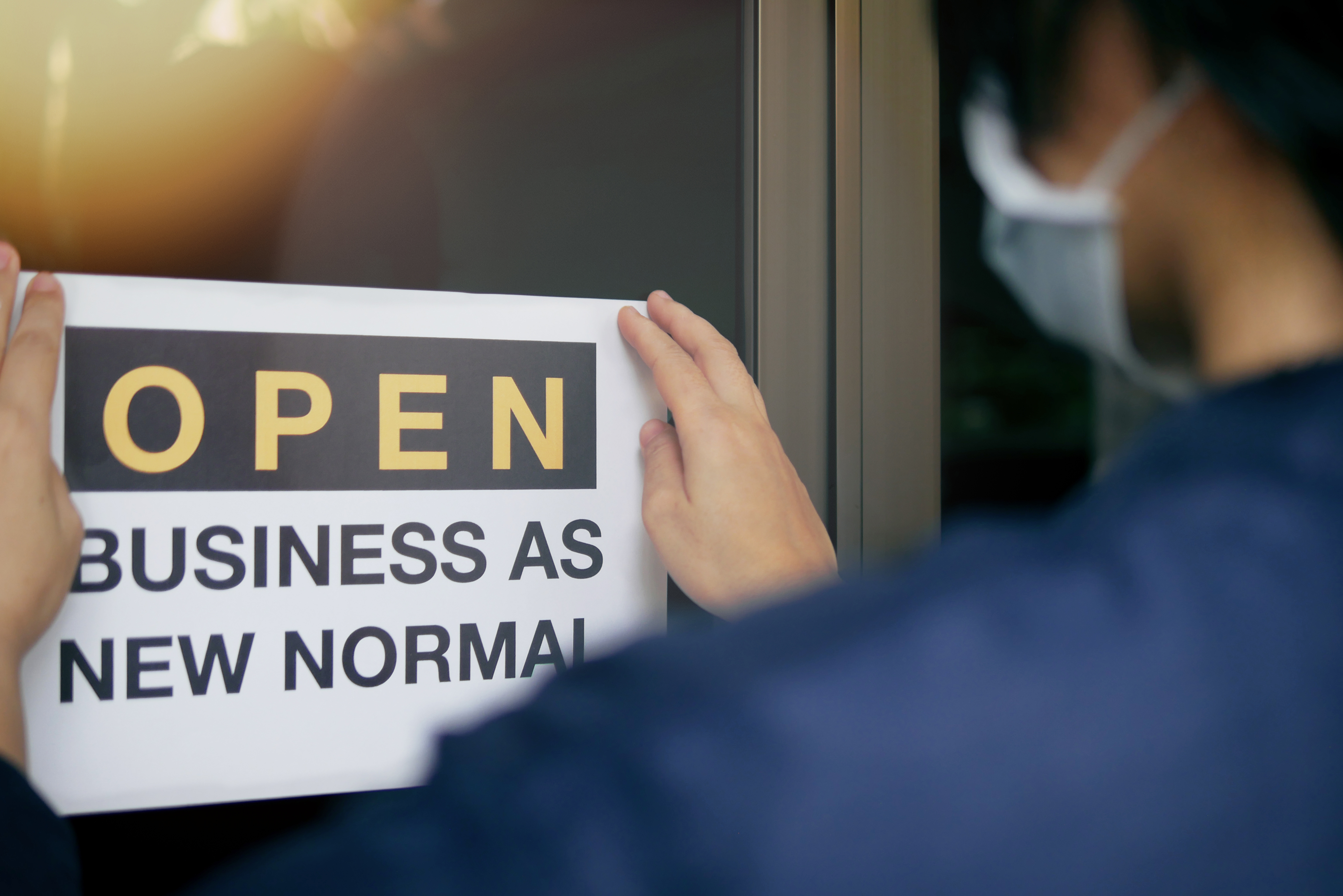 person with face mask putting up sign saying ;open business as new normal'