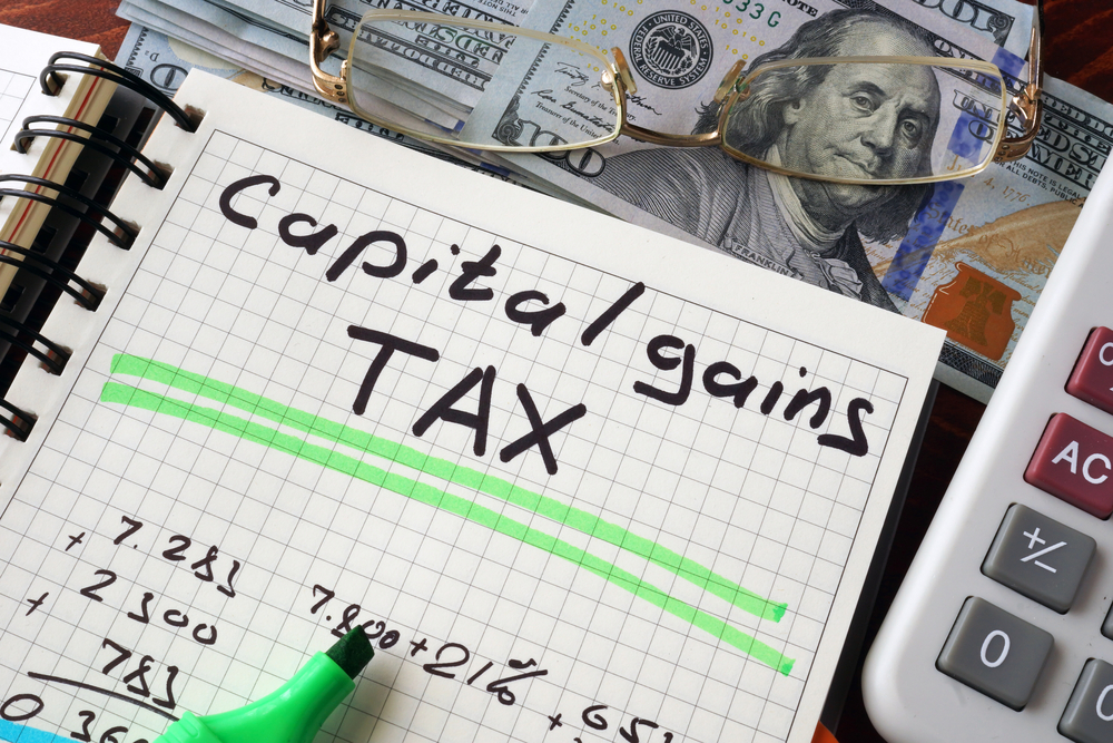 capital gains tax written on notebook surrounded by calculator and money