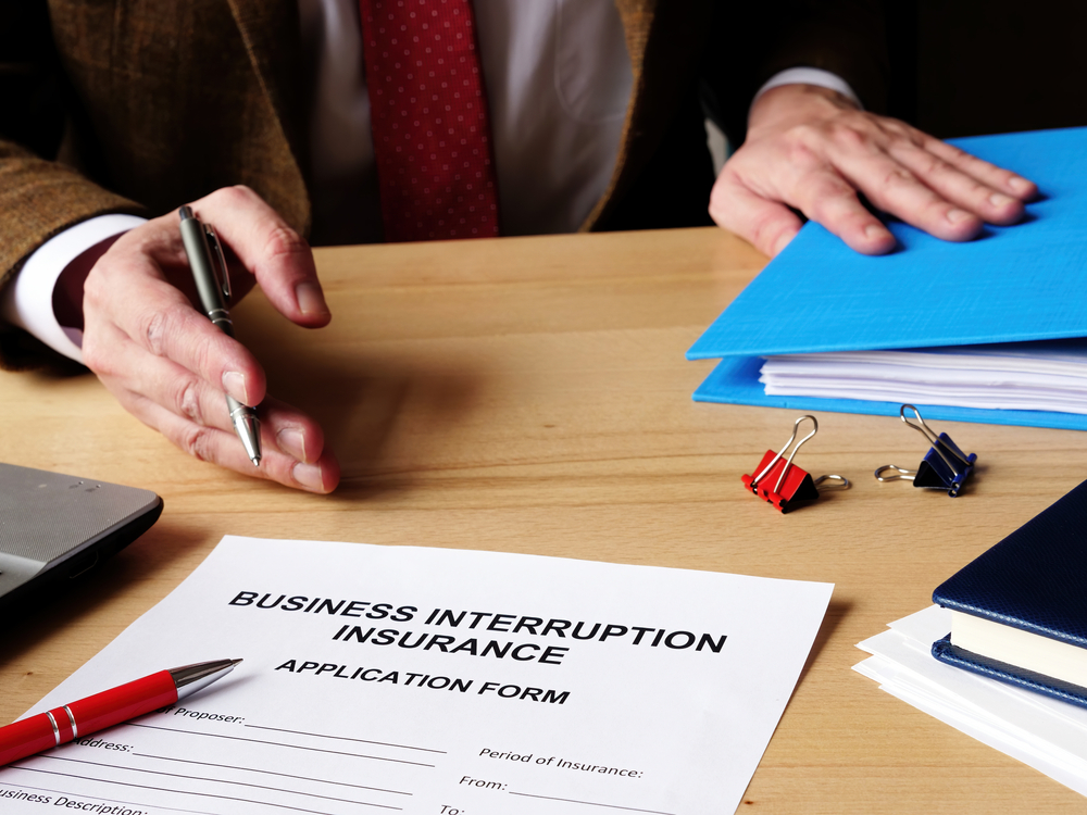 Man signing business interruption insurance application form